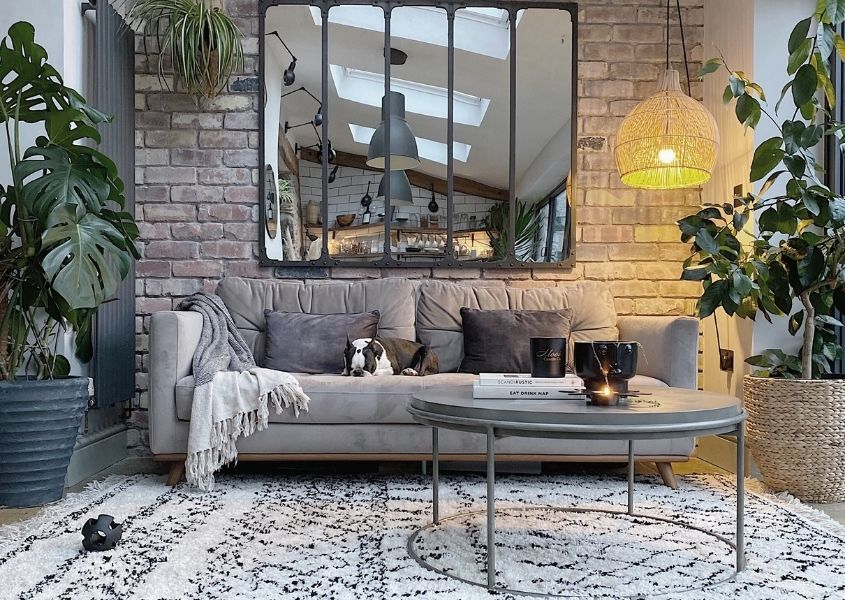 Grey sofa with white and black rug against a stone wall with a large leaded mirror
