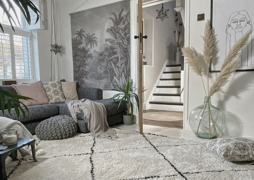 Living room with large cream rug, grey sofa, large glass floor vase with pampas grass and a grey mural on the wall