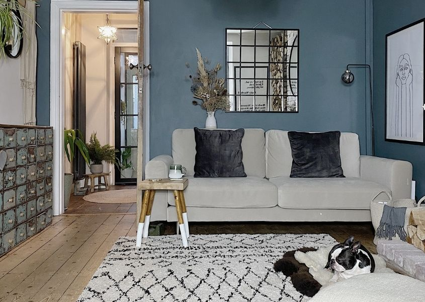 Living room with blue painted wall and large paneled mirror with cream sofa and wooden milking stool