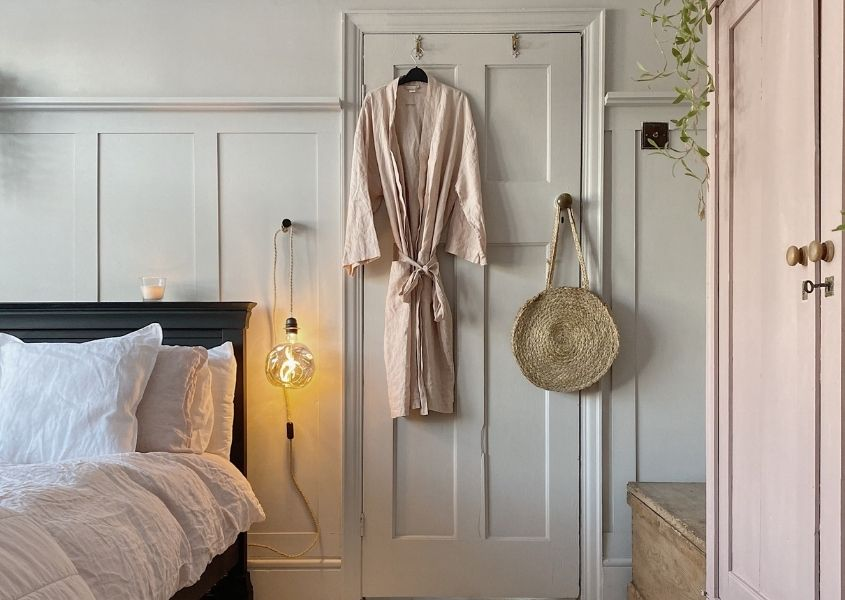 Back of white painted bedroom door with pale pink dressing gown hanging on it, with wood paneled wall and wooden bed