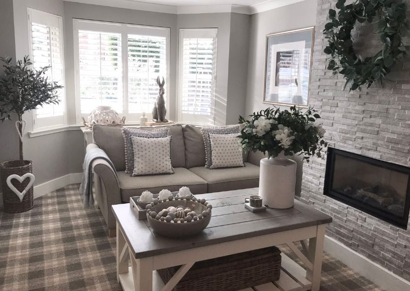 Living room with rustic coffee table and grey brick chimney breast with large bay window