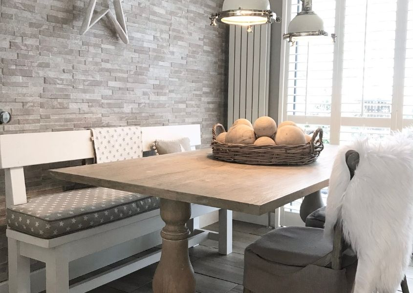 Refectory style wooden dining table with grey brick wall and white wooden bench