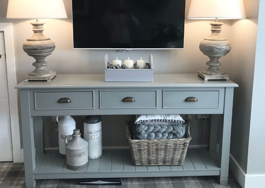 Grey painted wooden console table with three drawers and three draws with tv on top