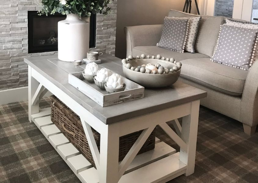 Wooden coffee table with white painted legs and white candle and ornaments on its surface