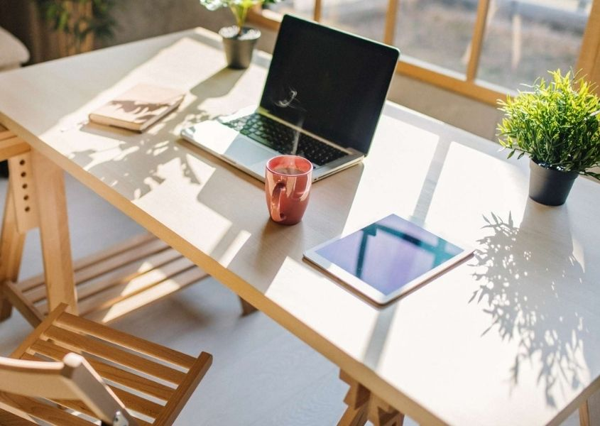 wooden desk with open laptop in front of large window