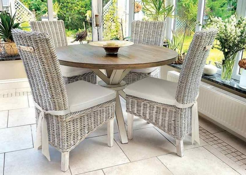Grey rattan dining chairs and a round wooden dining table