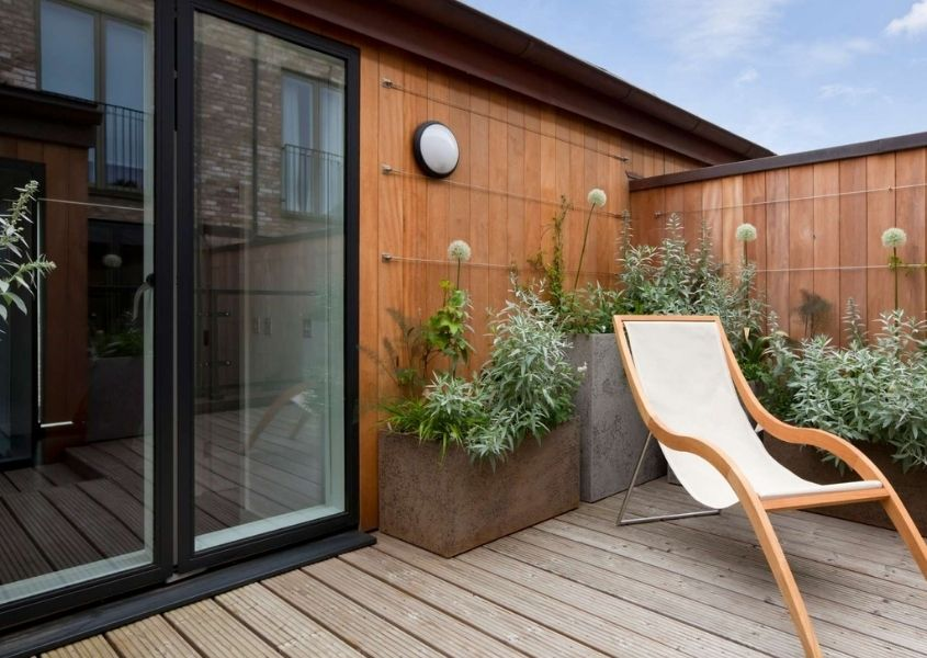 Decked outdoor patio with white deck chair and dark grey sliding patio door