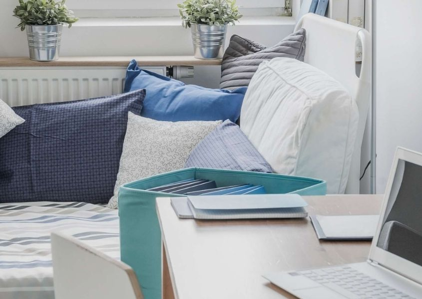 white day bed with blue cushions and throws