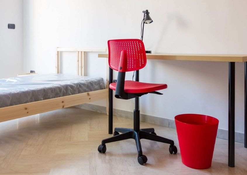 wooden single bed and white desk with red swivel office chair
