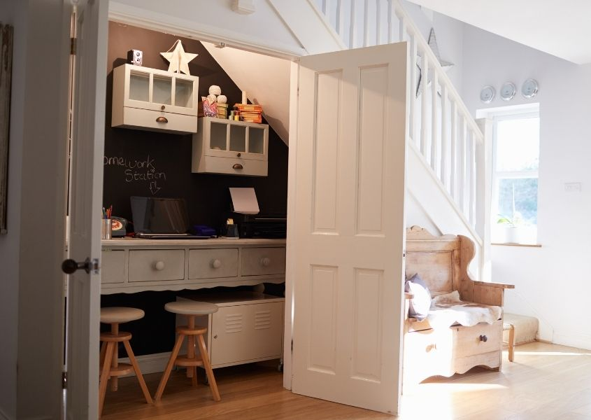 Home office in large cupboard under the stair with white painted wood doors