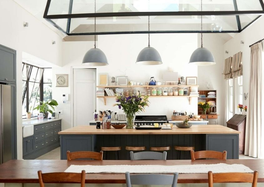 Large kitchen/diner with grey kitchen units, wooden dining table and three hanging ceiling lights in a room with a glassed pitched roof.