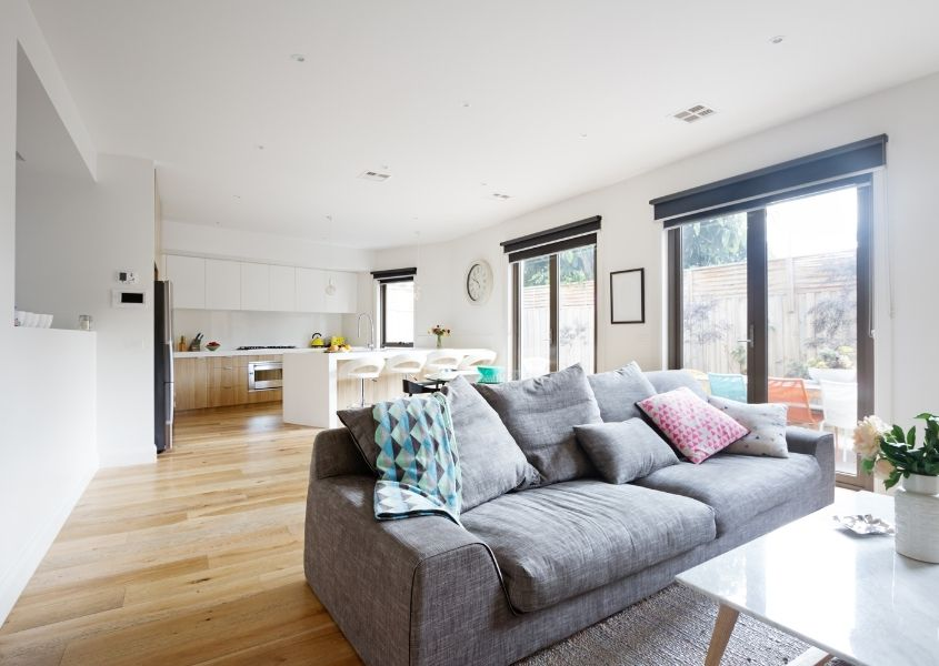 Open plan kitchen and living room with white kitchen, wooden floor and grey fabric sofa with large patio doors
