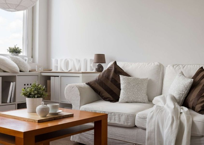 White living room with white fabric sofa, wooden coffee table and shelf with white painted wooden letters spelling Home
