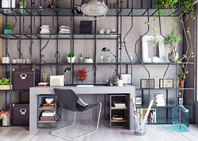 Concrete desk in front of a wall of metal pipe shelving filling entire wall with wires and hanging green plants