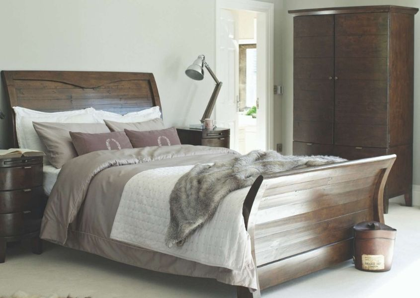 Large dark wooden bed with blankets and cushions, and matching bedside table and wardrobe
