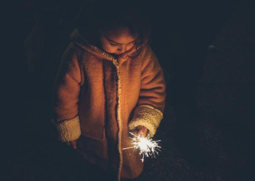 Young girl in thick coat holding sparkler in the dark