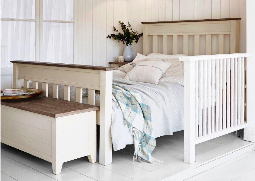 white painted reclaimed wood bed with matching wooden blanket box