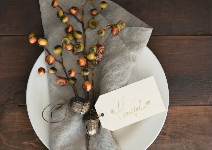 Napkin with bunch of dried berries tied with string and tag saying Thankful
