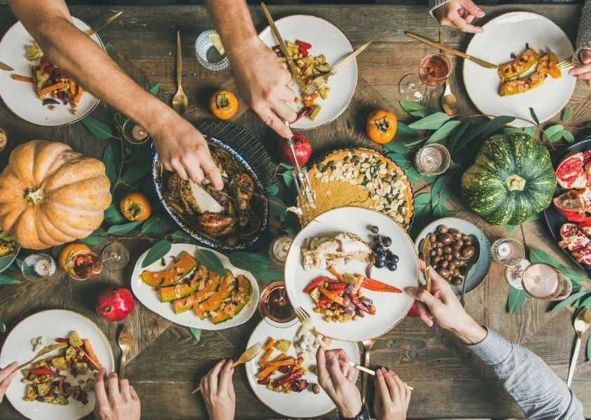 Close up of lots of different autumnal foods on a wooden dining table with people's arm serving