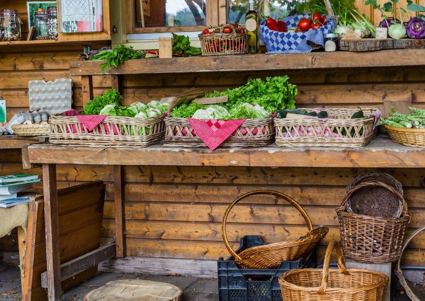Fruit and vegetables displayed on rustic table and baskets in a farm shop