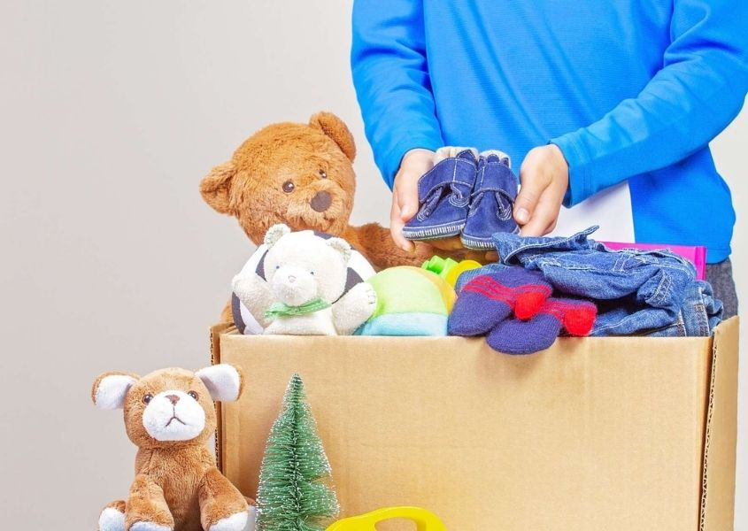 Child in blue jumper holding cardboard box of toys