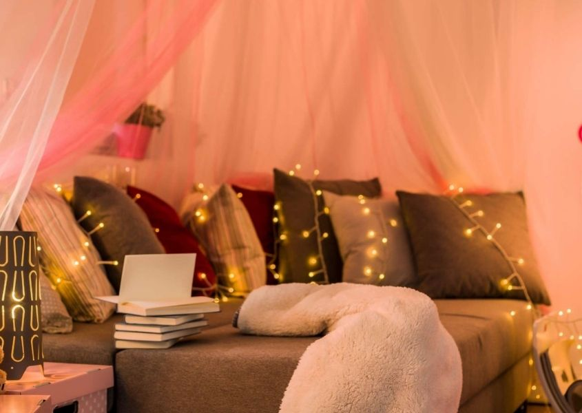 Bed with lots of cushions under sheer pink drapes