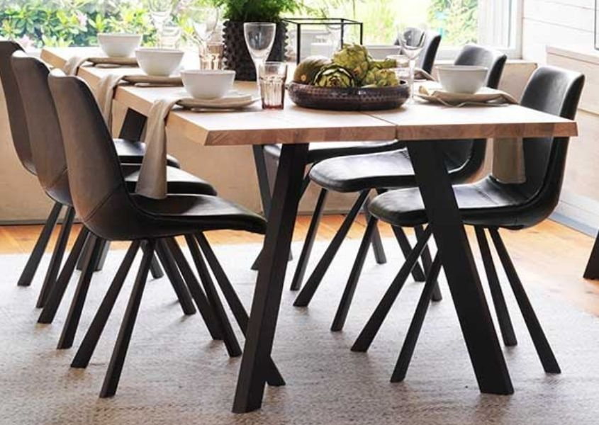 Industrial dining table with black metal legs and brown faux leather dining chairs
