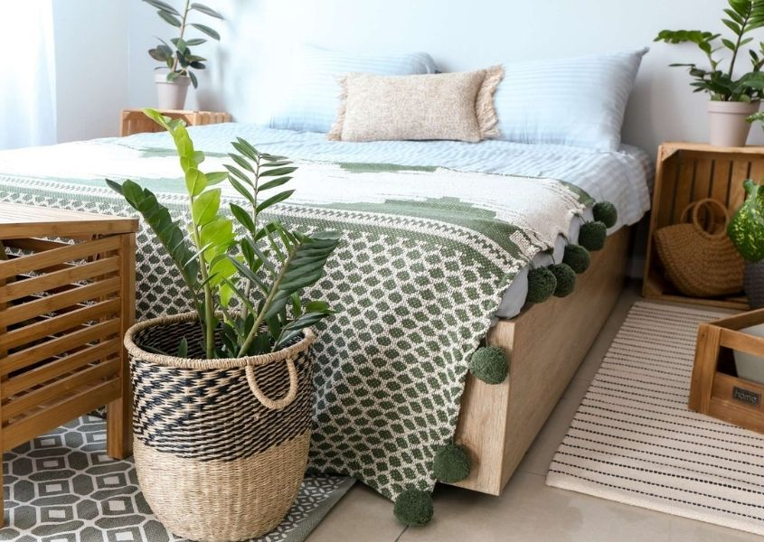 Plant in wicker basket at the foot of a wooden bed frame
