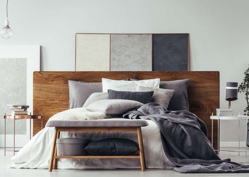 Grey bedroom with wooden bed and stool and at end of bed with white and grey covers