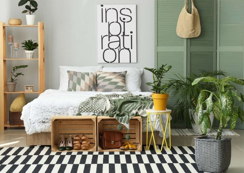 Contemporary bedroom with wooden palette boxes for shoe storage, black and white rug and green painted shutter screens behind bed
