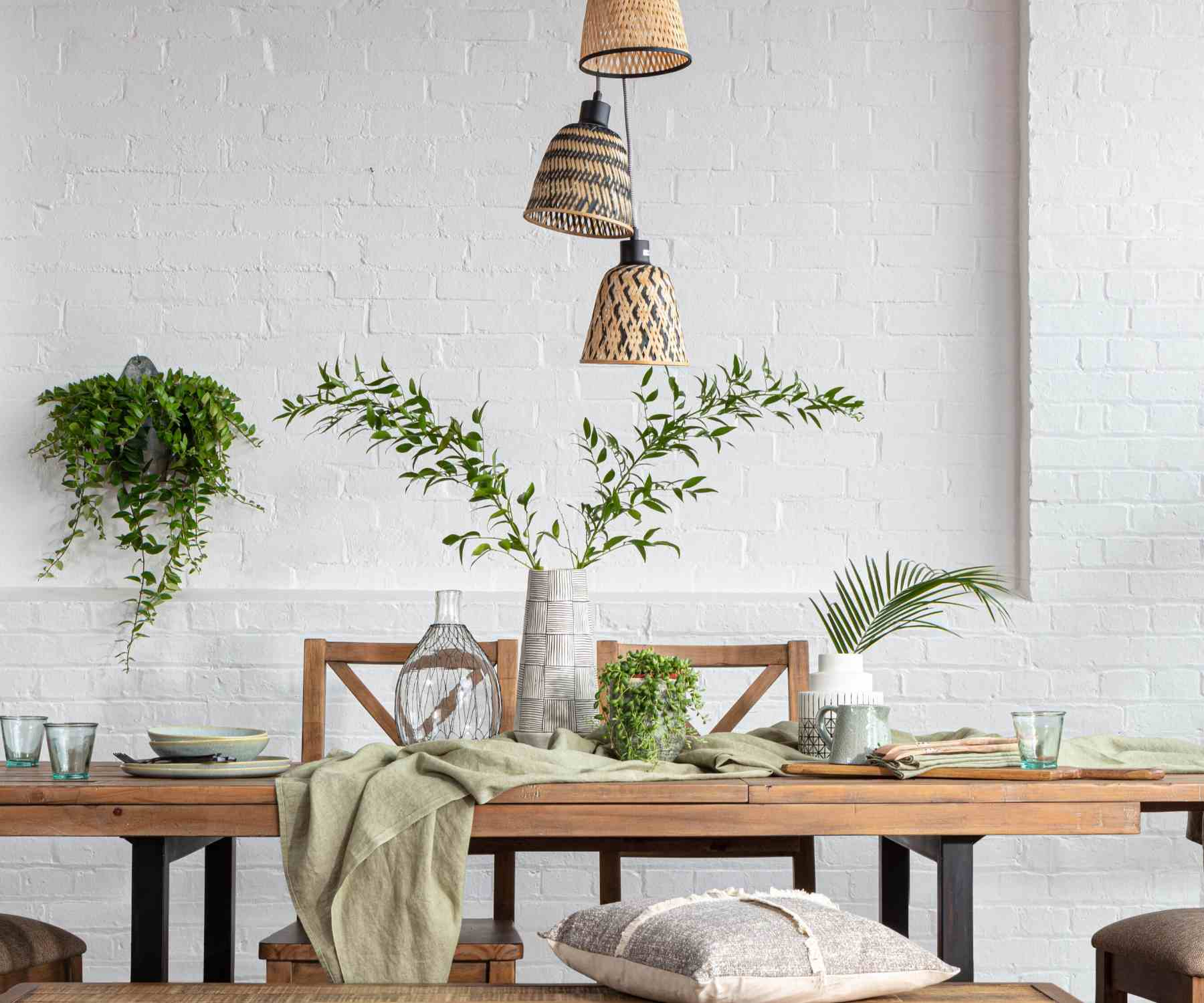 Green plants on reclaimed wood dining table and on white brick wall