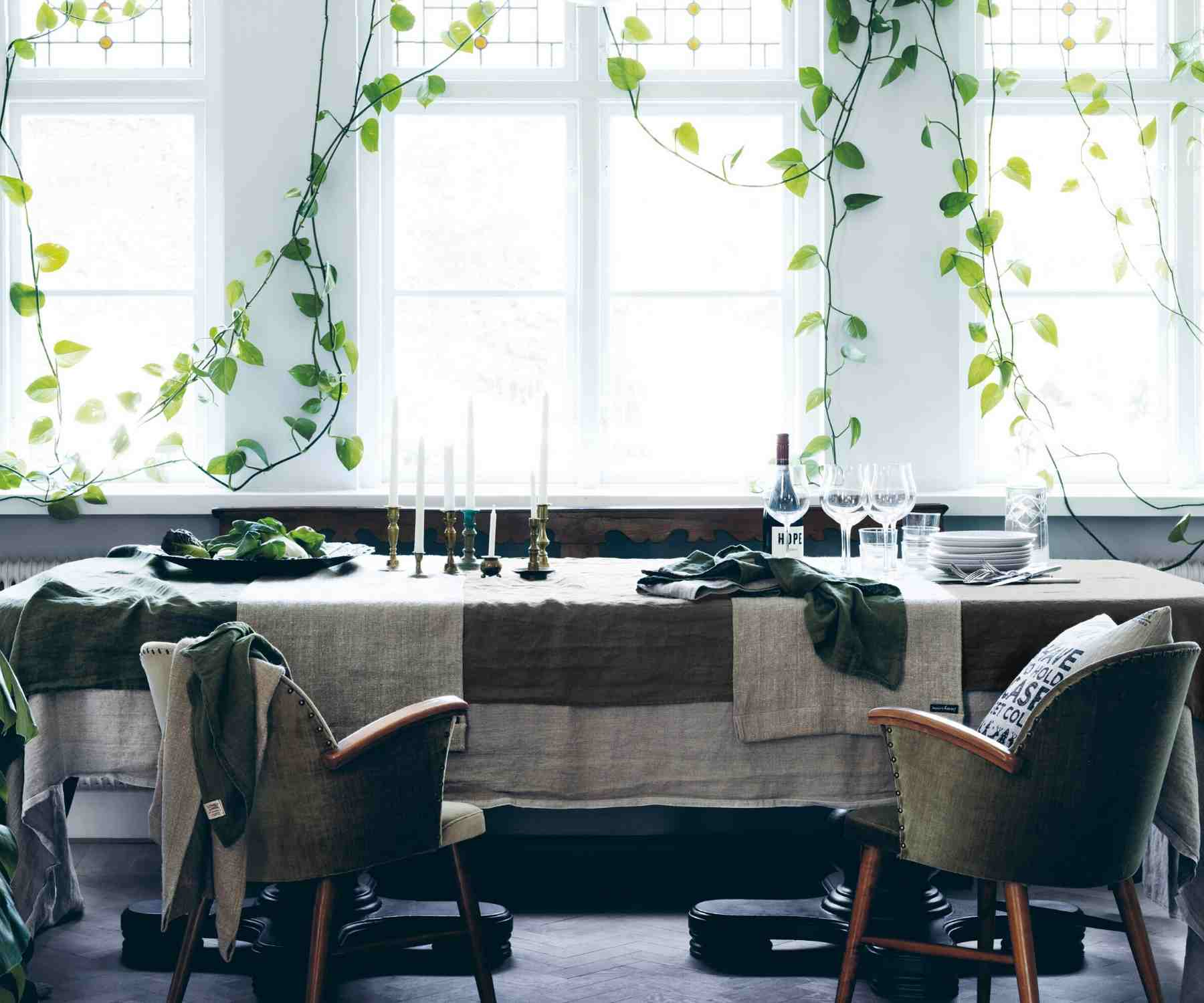 Large table with layered linen tablecloths in front of large window