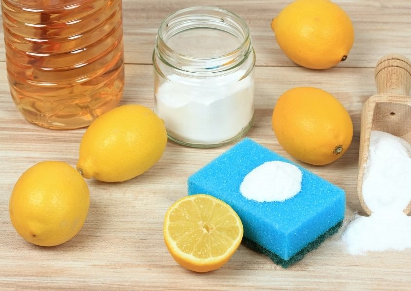 Whole and cut lemons with glass jar of white powder and plastic bottle of vinegar with a blue sponge