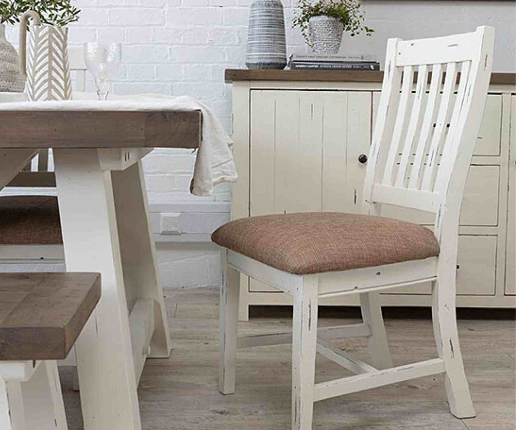 White wooden dining chair with beige padded seat next to white dining table