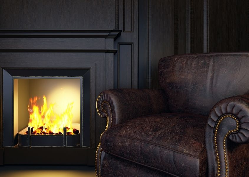 dark painted room with fireplace and dark brown leather chesterfield armchair