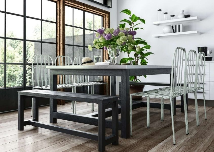 Square grey wood dining table with grey wooden bench and white chairs