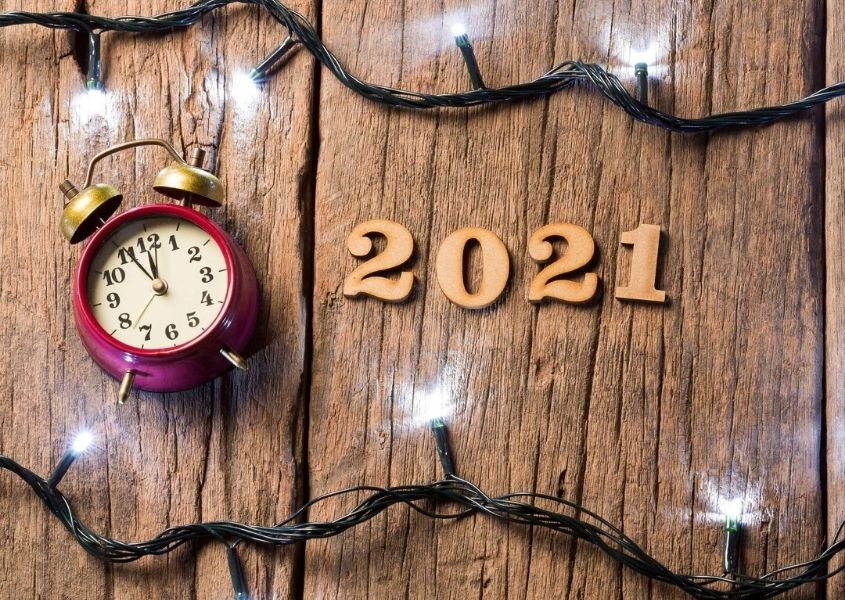 Alarm clock and wooden numbers spelling 2021 against rustic wood background