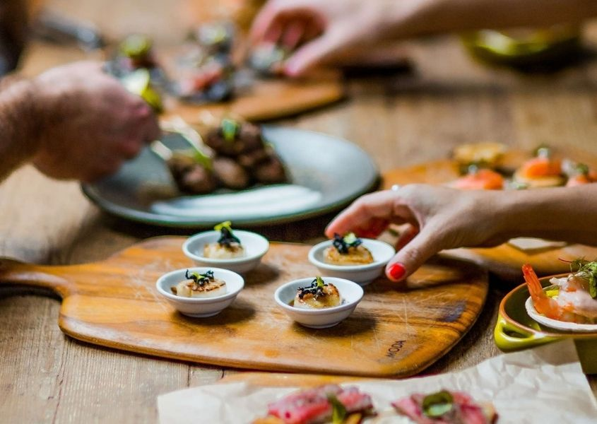 Wooden serving board with canapes on and handing picking up food on wooden dining table