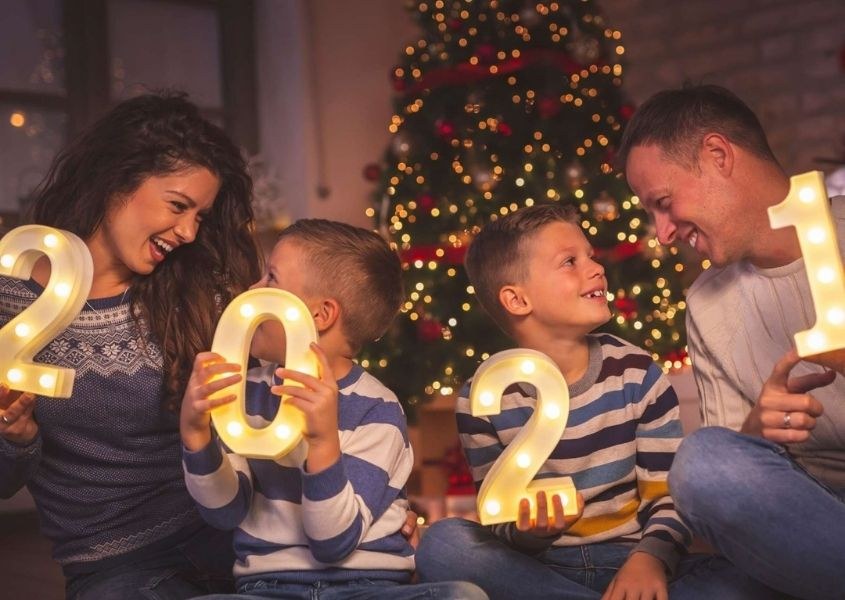 Family of mum, dad and two children each holding a number spelling 2021 sitting on a sofa
