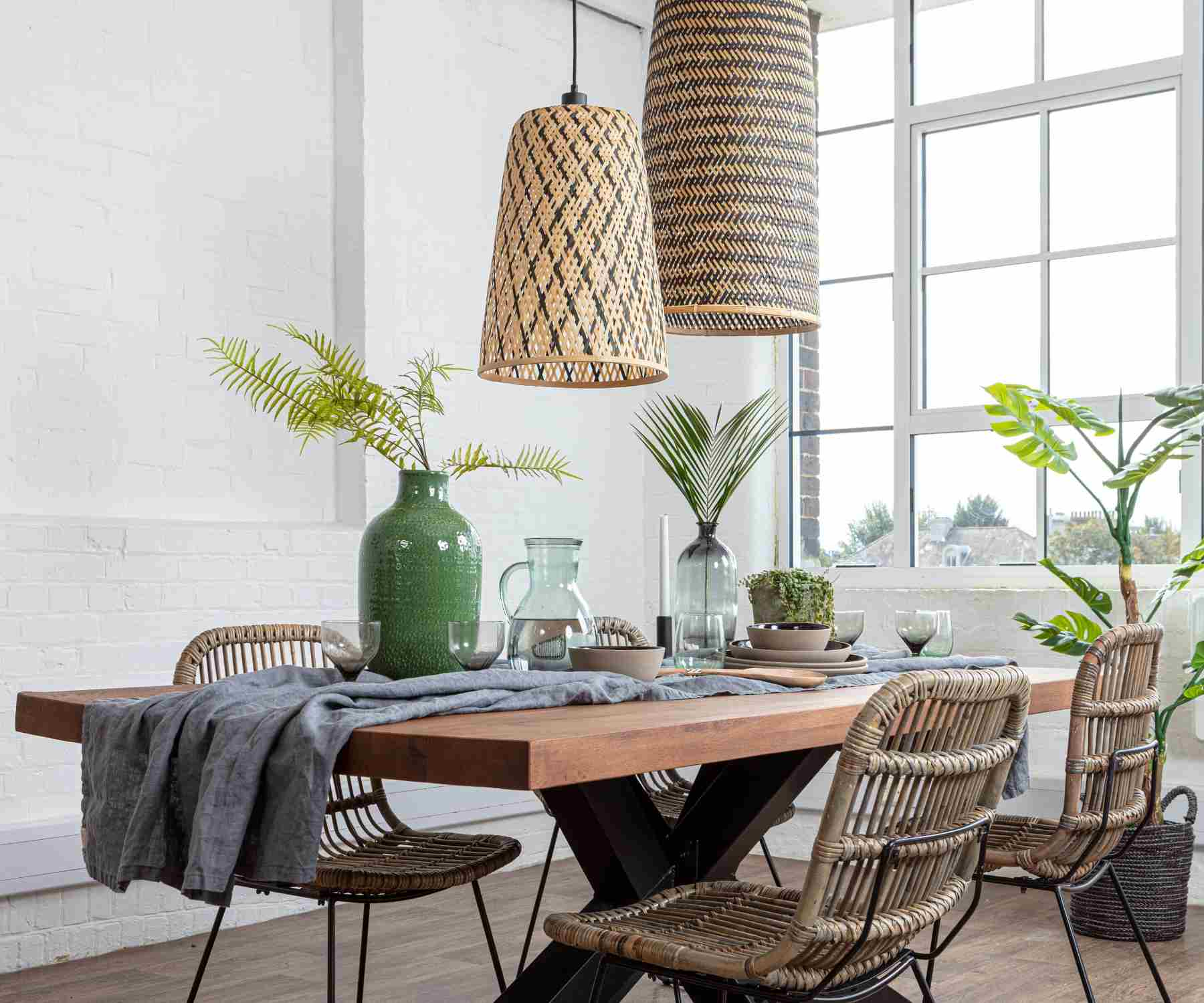 Two bamboo hanging pendant lights above an industrial dining table