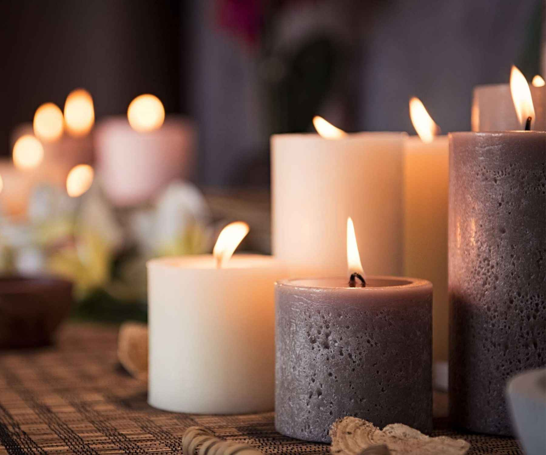 Close up of three lit candles on a wooden table