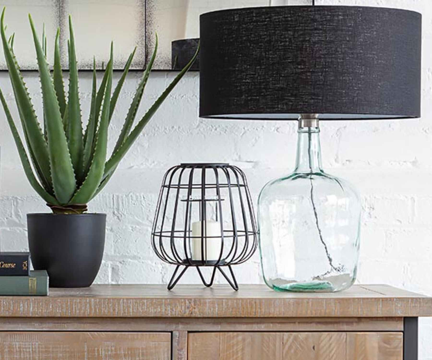 Glass table lamp on wooden sideboard with aloe vera plant