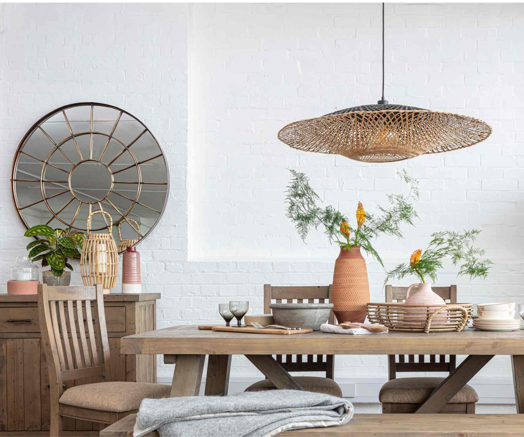 Round wall mirror next to reclaimed wood dining table with hanging pendant light