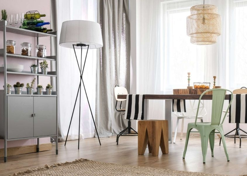 Grey bookcase with cupboard doors in living room with floor lamp and dining table