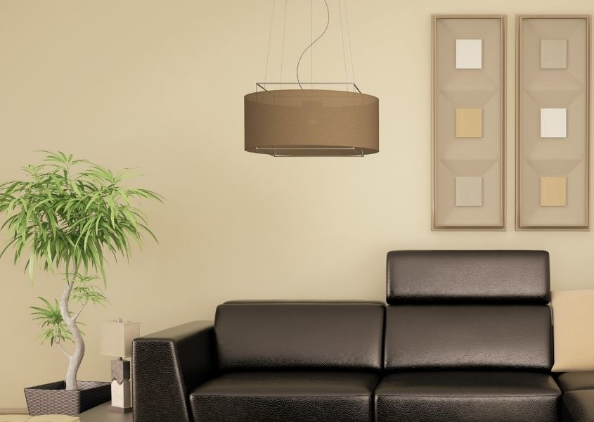 Stone painted living room wall with brown pendant light and dark grey leather sofa