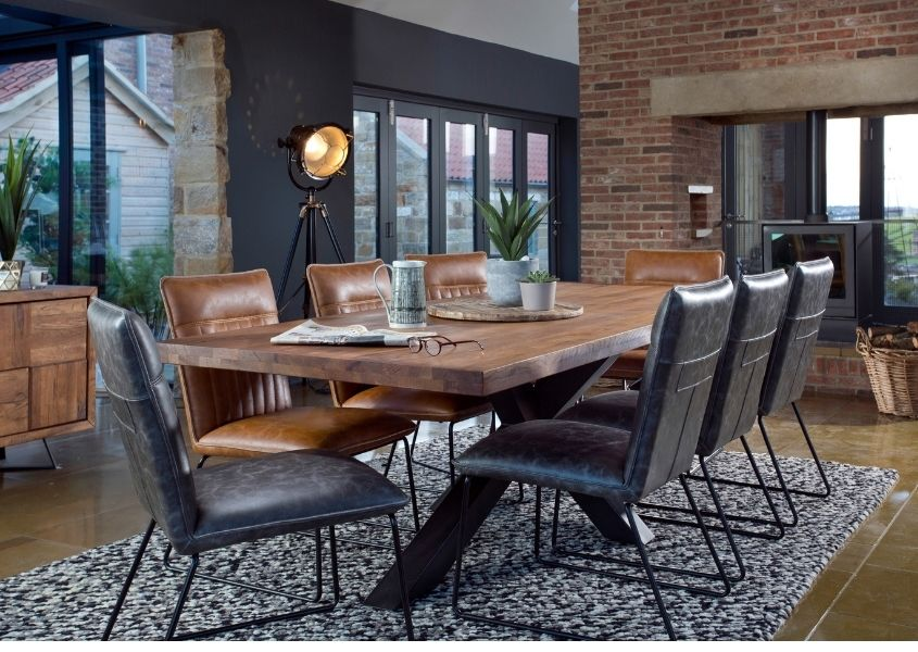 Large reclaimed wood dining table with grey faux leather chairs in industrial style dining room