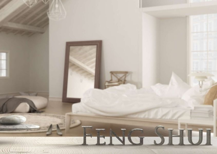 Bedroom with white bed and large floor mirror with words feng shui