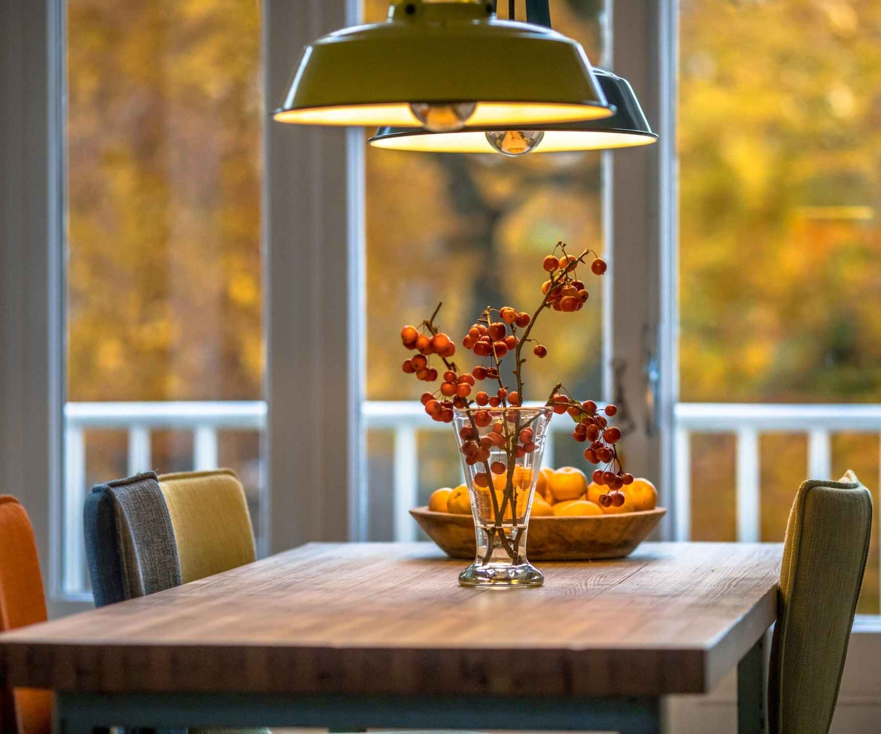 Wooden dining table with green pendant lighting and autumn berries