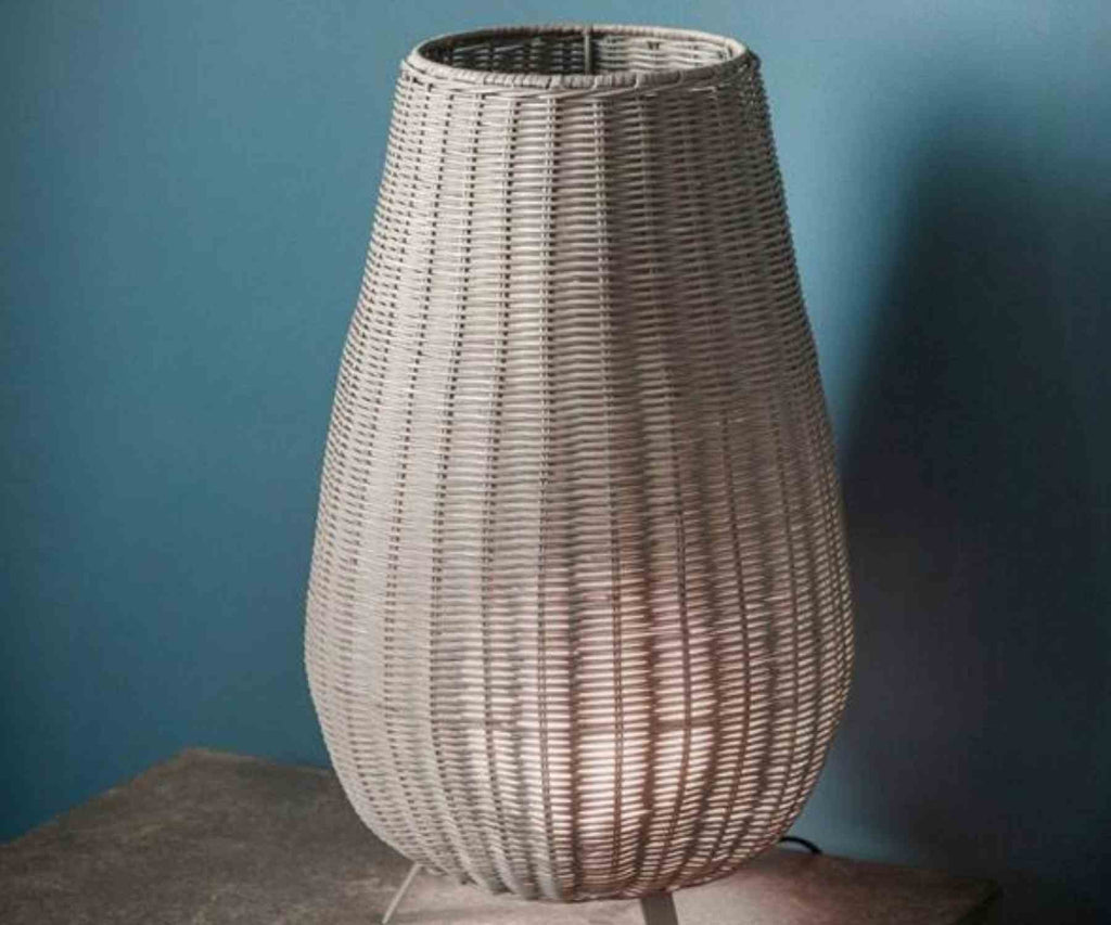 Grey wicker table lamp against blue wall
