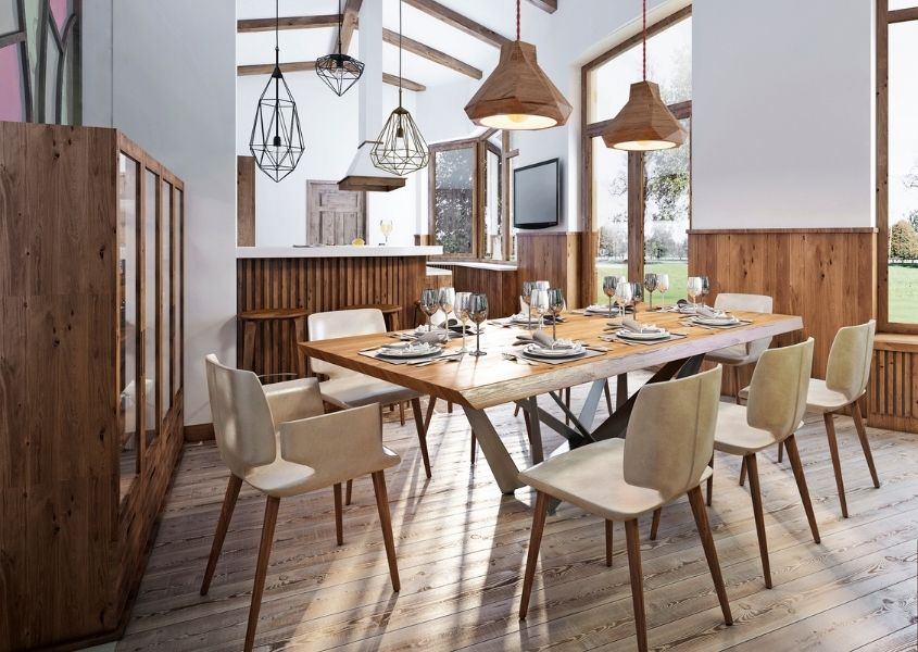 Large wood dining table with wooden chairs in bright dining room with wooden hanging pendant lights